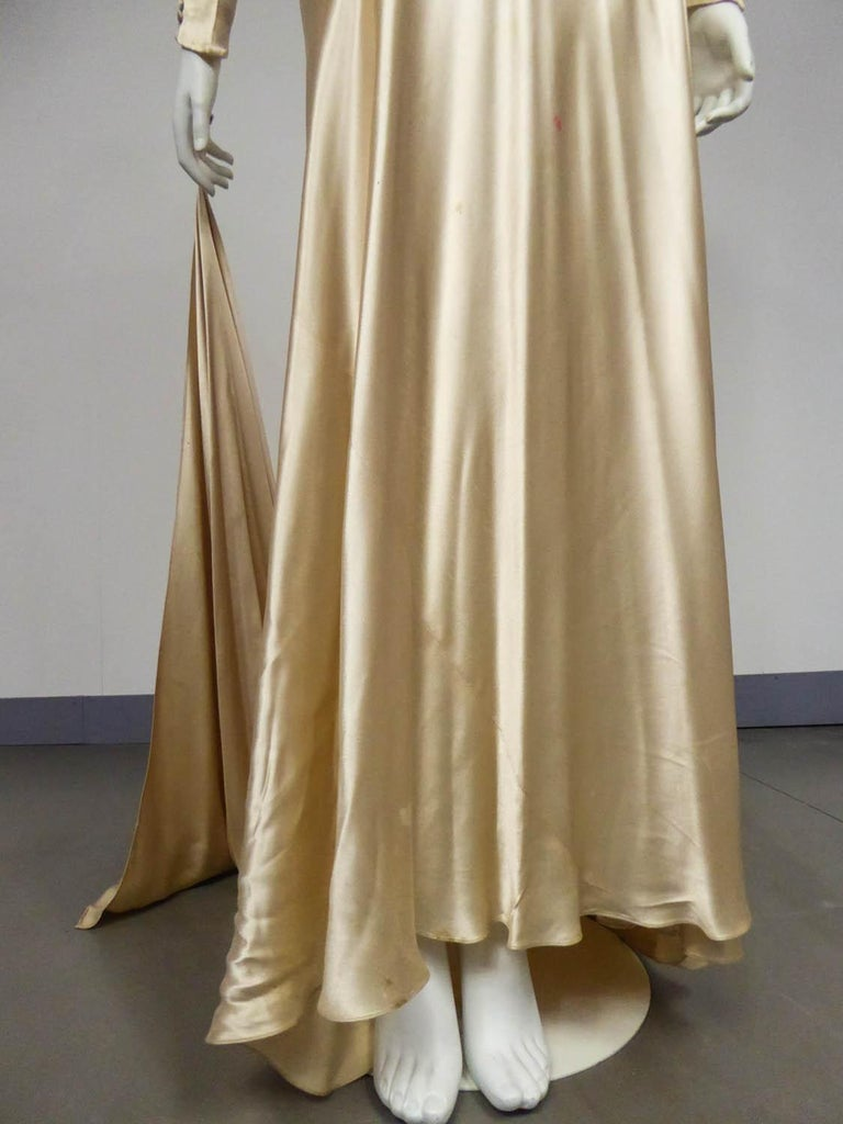 Circa 1935/1945 France  Wedding dress in champagne silk satin from the late 1930s. Fluid and skin-tight cut in bias with a pleated work on the chest highlighting a sheath silhouette. Long sleeves adorned with a long row of matching buttons and