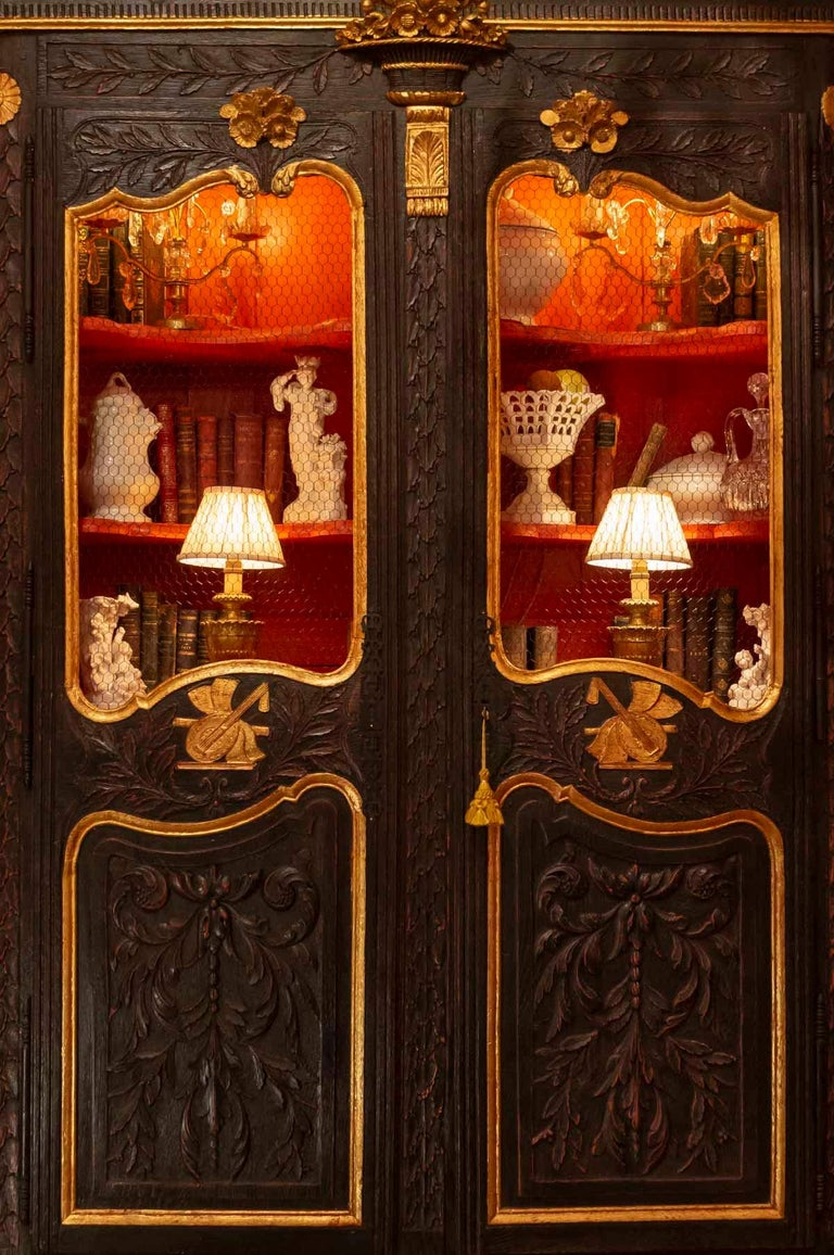 Marriage cabinet transformed into a library in antique oak and gold leaf, early 19th century, with musical instrument decoration, mesh, 4 shelves Measures: H 220cm, W 130cm, P 49cm.