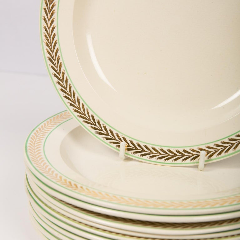 We are pleased to offer this set of a dozen early 19th century Wedgwood creamware dessert or salad dishes decorated with a border featuring gold chevrons set between two enameled green lines. The creamware body has a warm look. The elegant gold