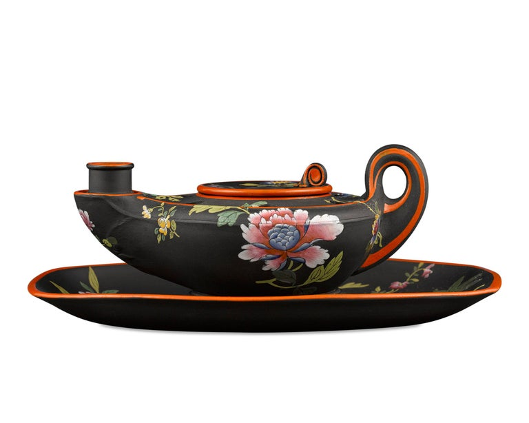 This enchanting antique Wedgwood black basalt inkwell is crafted in the form of an ancient oil lamp. With a removable well and holes for storing pens and quills, it is decorated with exquisitely hand painted enamel in a Chinese-inspired floral