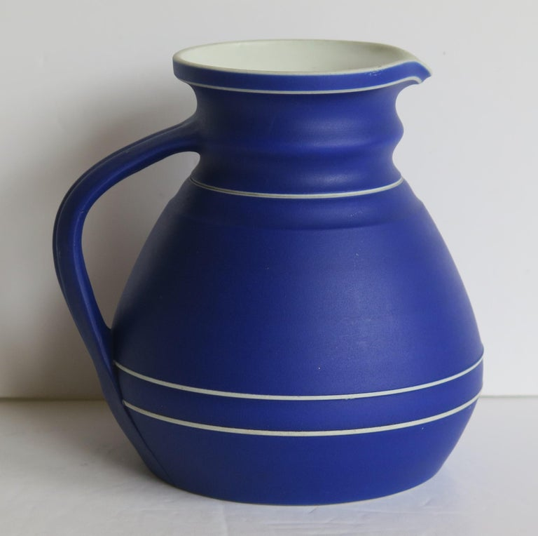 This is a fine early Jasperware stoneware water jug or pitcher in the rarer dark blue ground, made by WEDGWOOD, England in the mid 19th Century, 1850 