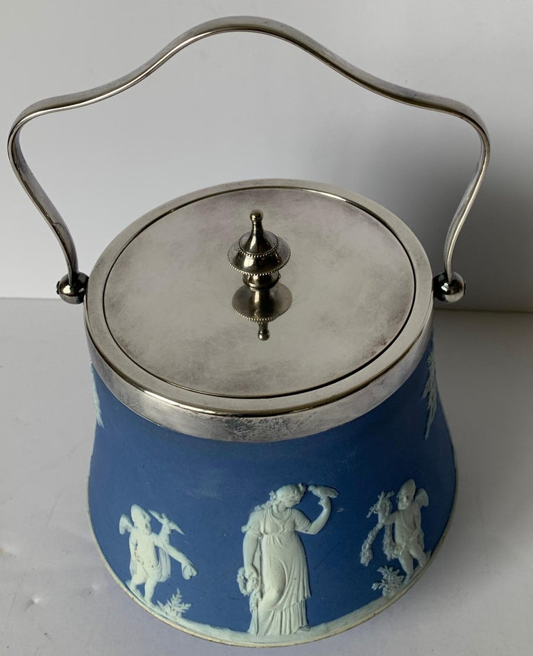 Wedgwood light blue bell shaped jasperware biscuit barrel overall neoclassical motif with a silver plated lid and handle. Stamped Wedgwood on the underside and lid is marked.