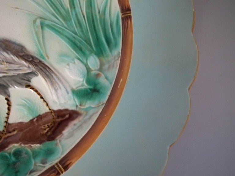Wedgwood Majolica plate which features a heron at the edge of a pond. Designed by Joseph Theodore Deck. Colouration: pale blue, green, cream, are predominant. The piece bears maker's marks for the Wedgwood pottery. Bears a pattern number, '864'.