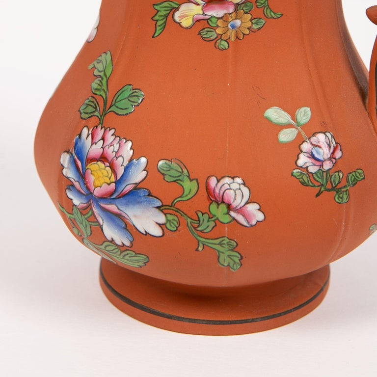 Provenance: With a paper sticker from the Polikoff Collection #252 Wedgwood made this lovely Rosso Antico pitcher circa 1850. It is decorated with enameled Chinese style peony flowers. When he created this design circa 1810, Josia Wedgwood II
