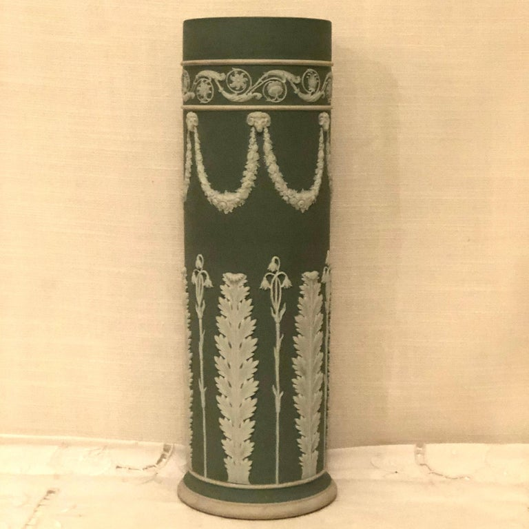 Wedgwood tall green jasperware vase with a rare decoration of rams heads, lilies of the valley and acanthus leaves. It was made before 1890. It is 11.75 inches tall. It is a perfect vase for a beautiful flower arrangement. Price-$1200.00.