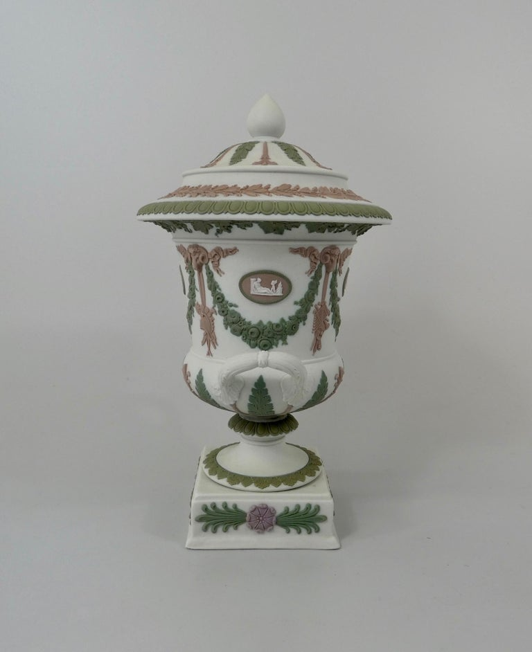 A fine Wedgwood 'Three colour' pottery vase and cover, circa 1900. The vase, sprigged with four lilac oval medallions, containing Classical figures, within flowering green swags, suspended from lilac rams heads, which also support hanging ribbons,