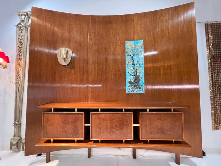 Hans Weiss (1900 to ?) and William Basser (1900 to 1958) of Weiss & Basser interior designers, New York, NY curved walnut wall unit mounted with floating sideboard consisting of three cabinets apparently supported by brass standoffs between an upper