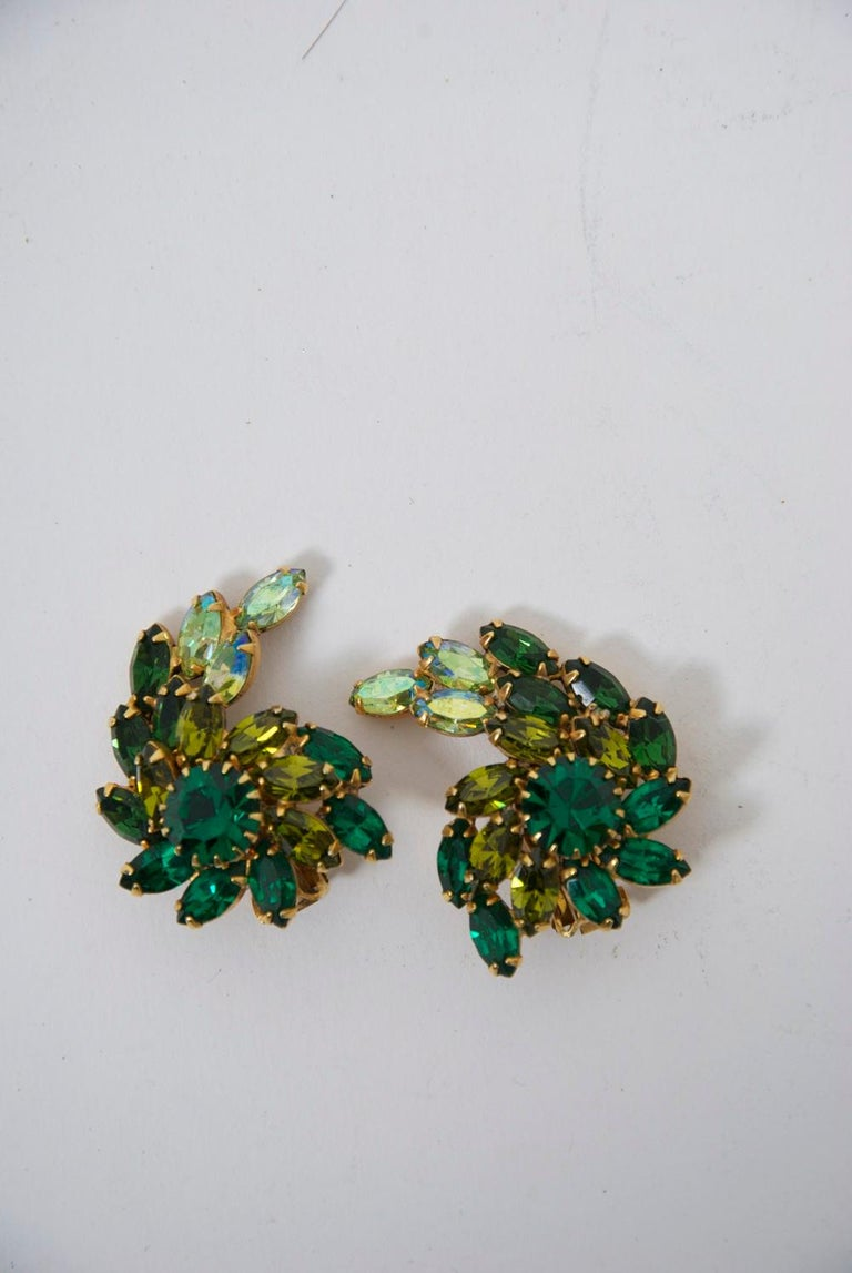 Weiss vintage clip-on earrings featuring two shades of green crystals, emerald and pale green of marquise form, their crescent shape centering a larger round emerald stone. The earrings complement the contour of the ear. Signed