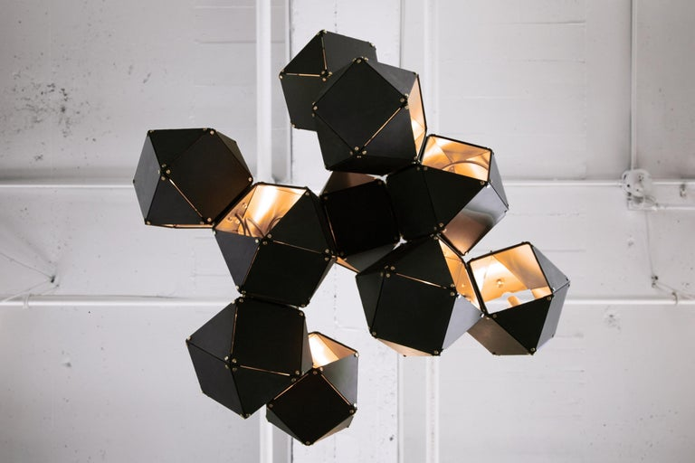 A fixture of metallic proportion, Gabriel Scott's signature Welles is a modern piece that showcases expert artistry. Hollowed metallic polygons branch out into a modular system of interconnected configurations for a stunning optical illusion. With