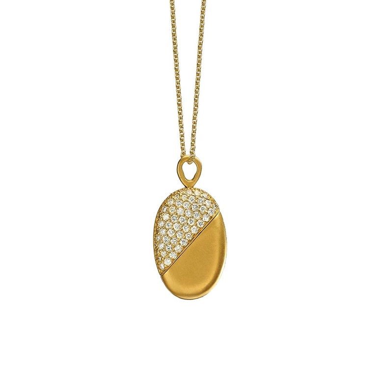 Pendant twists from heart shape to oval and back. 18K yellow gold with satin finish. 1.1 carats of white diamonds. 16