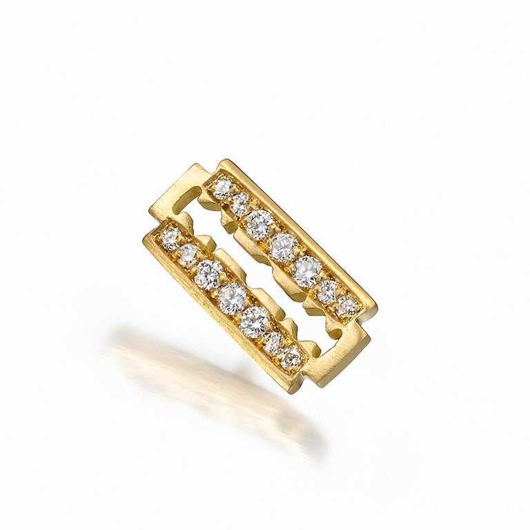 A trio of earrings in 18K yellow gold. Anarchy symbol stud earring has 16 diamond rounds totaling 0.04 carats (E/F, VS1/VS2). Razor blade stud earring has 14 diamond rounds totaling 0.5 carats (E/F, VS1/VS2). Safety pin earring has 0.12 carats of