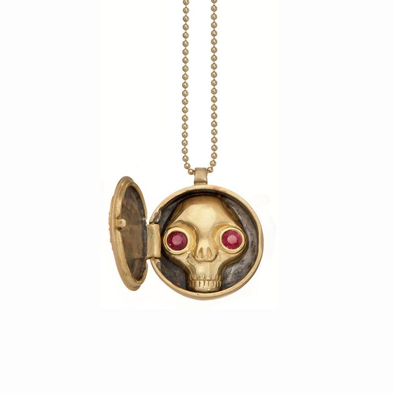 Locket necklace opens and closes. Inside of the locket is a ruby-eyed skull. 18K yellow gold, satin finish. Rubies form a beautiful heart shape. 16
