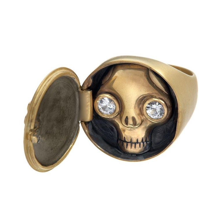 Locket ring opens to reveal a skull. 18K yellow gold, satin finish. White diamonds (outer, bones shape), totaling approximately 12 points. White sapphires (inner, eyes), totaling approximately 30 points. Size *6. Limited-edition, number 3 of 3. Made