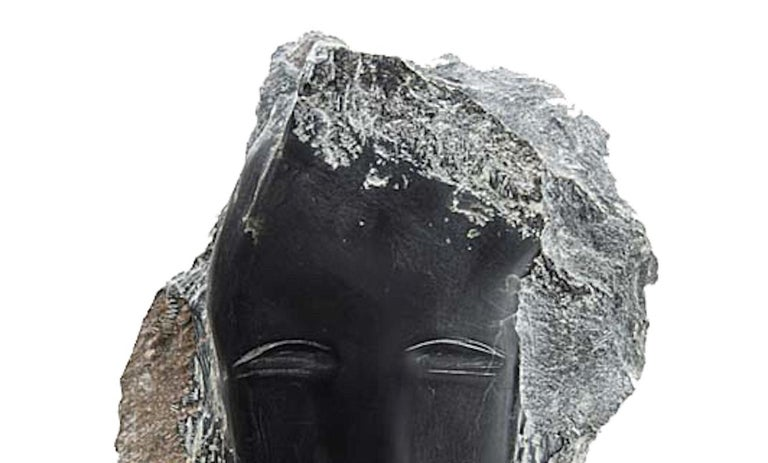 Contemporary American sculptor Wendy Hendelman's Black Alabaster Head Sculpture on a black marble base. Hendelman's work reflects her love of the primitive and the ancient. The small scale and style have established her identity as a sculptor as was