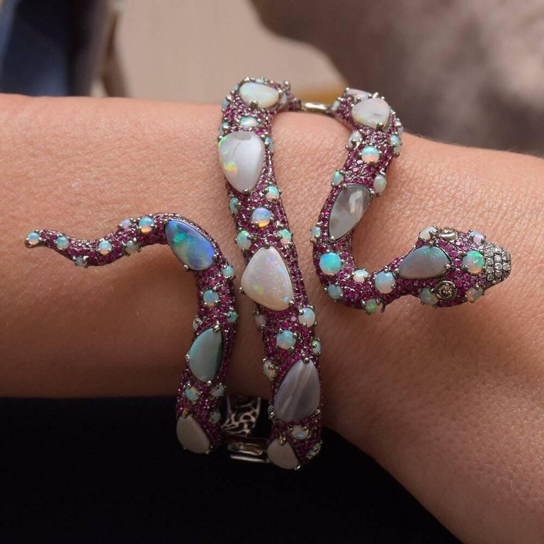With a fascination of exotic landscapes and wildlife, Wendy Yue's jewelry radiates opulence and whimsical characteristics with a wide range of color and details. This one-of-a-kind Wendy Yue pavé ruby serpent cuff is accented with white opals and