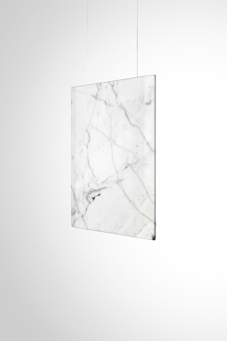 Structure composed of a thin square in marble, double emission of LED light, suspension with steel wires.  A lamp with an essential geometry that enhances the quality of handcrafted marble and the high technology of the LED lighting system.  An