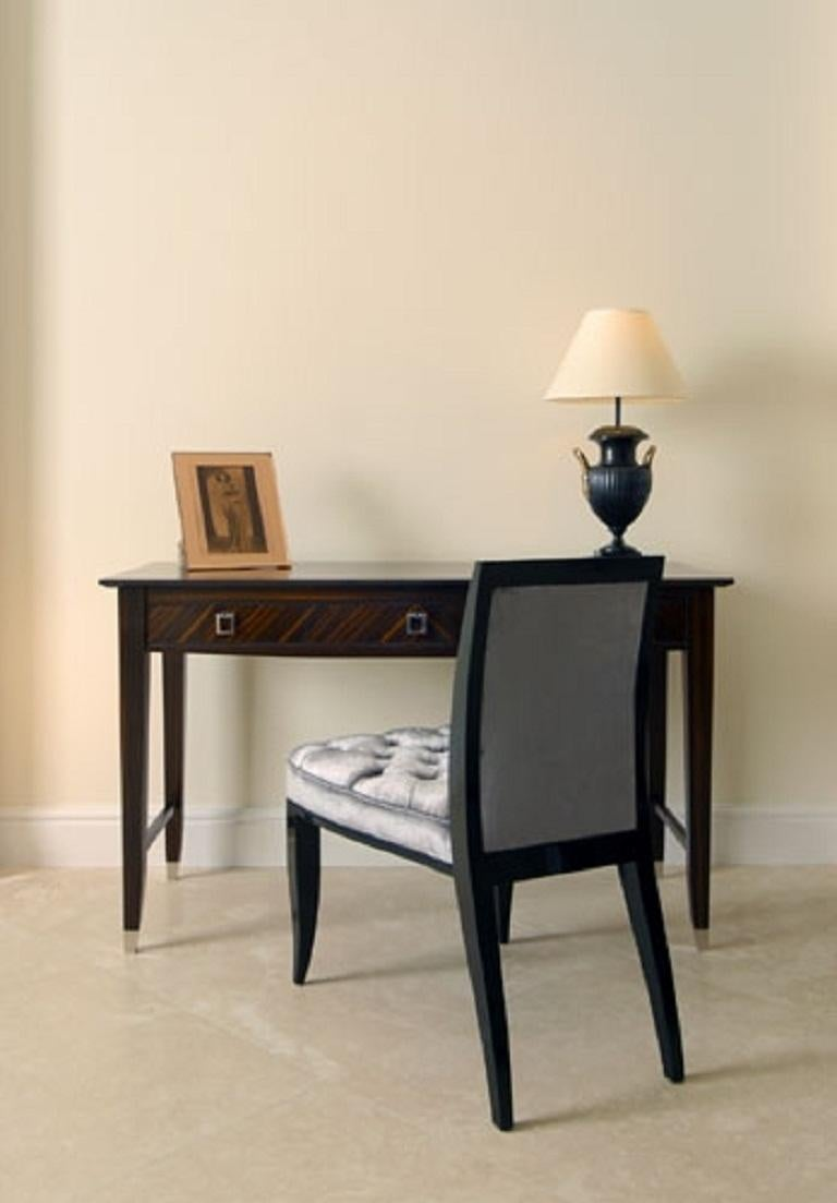 An elegant writing or dressing table finished in Macassar ebony.  Beautiful and versatile this table consists of three drawers with smart drop handles finished in polished nickel. The table stands on four elegant shaped legs fitted with polished