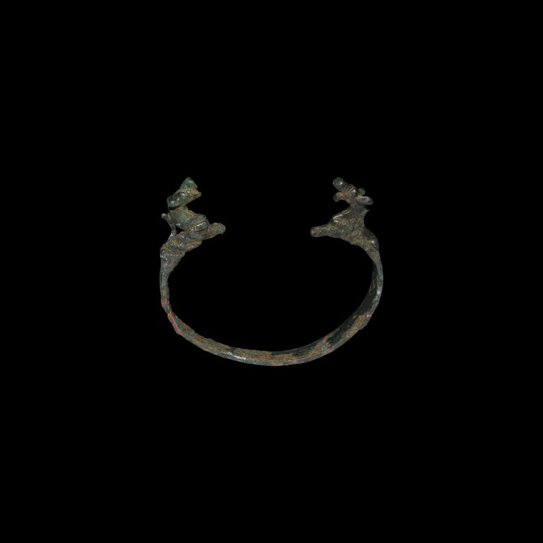 A bronze bracelet with flat section band, terminals formed as recumbent quadrupeds, accompanied by a typed and signed note by the late W.G. Lambert, Professor of Assyriology at the University of Birmingham, 1970-1993, which states: 'Bronze Bracelet,