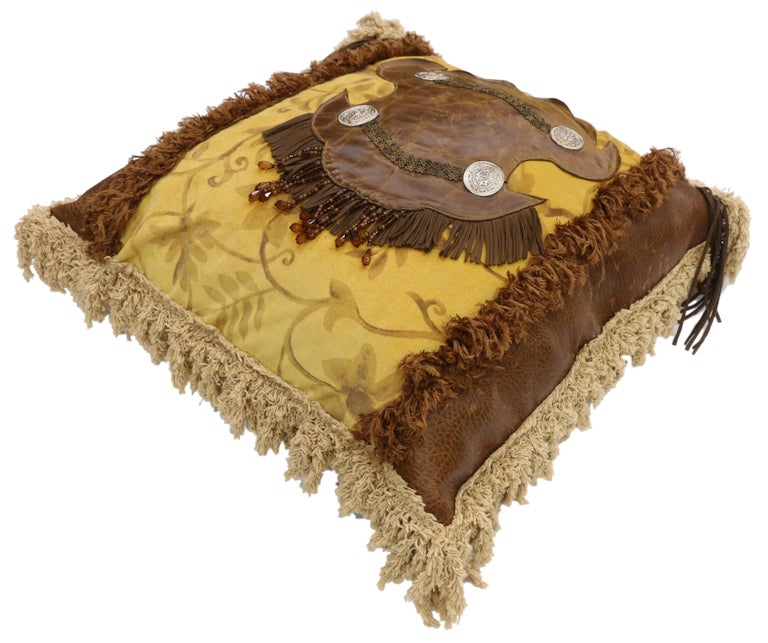 Western Rockabilly style leather throw pillow with fringe and tassels. This Western style throw pillow features a golden yellow fabric backdrop with a leather centerpiece adorned metal accents, fringe, and beads. The golden yellow center is flanked