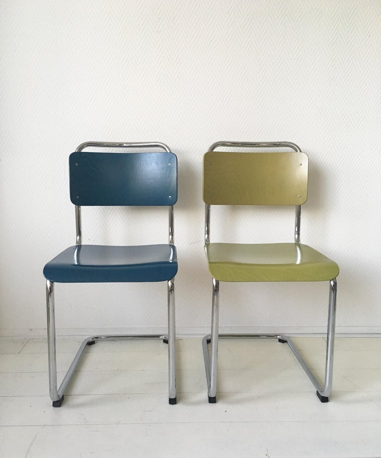 This wonderful set of four tubular dining room chairs, consist of two yellow pieces and two blue ones. They were designed by W.H. Gispen in the 1930s. Produced by license of Gispen International B.V. to B.V. Gebroeders van der Stroom. The pieces are