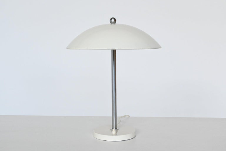 Very nice mushroom shaped white table or desk lamp model 5015 designed by W.H. Gispen and manufactured by Gispen Culemborg, The Netherlands 1950. This lamp has a white lacquered round weighted base with a brushed steel bar and an original white
