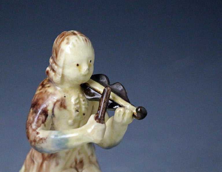 Early English pottery Staffordshire figure of a seated violinist. The figure is made with two colored clays in the Astbury- Whieldon style. A rare and charming piece from the early days of the Potteries.  Dimensions: 2.00 inch wide 5.00 inch high