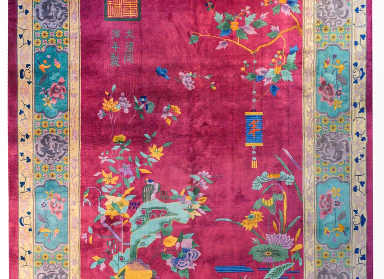 A whimsical early 20th century Chinese Art Deco rug with a peaceful garden landscape depicting a flowering tree branch with a lantern hanging over the corner of a pond with blossoming lotus and scholar's rocks, all on a bright cranberry background