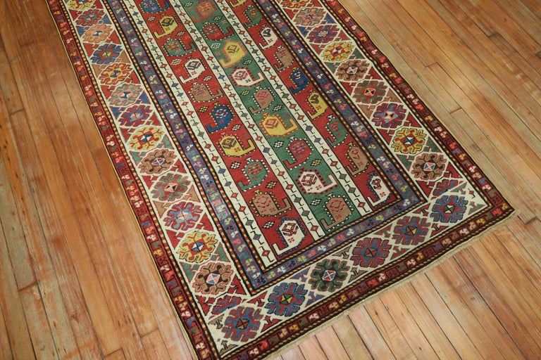 """A geometric looking Caucasian Kazak runner in tomato red, green dominant accents. The colors are lively, the design is unique. A connoseuirs dream.  Measures: 3'10"""" x 8'2""""."""