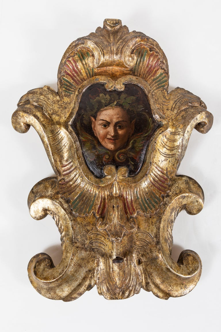 Charming, early 19th century, hand carved, gessoed, and 22-karat gold gilded, polychrome wall plaques featuring nature spirits surrounded by foliate wreaths. Each with wonderful, mischievous expressions.