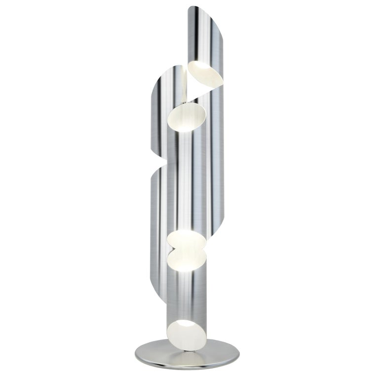 Inspired by church organ pipes, this seven-foot sculptural floor lamp is fabricated in satin stainless steel. Incandescent light fills each tube and flows out from strategically placed slits creating a warm and inviting Ambience. Designed in 2009.