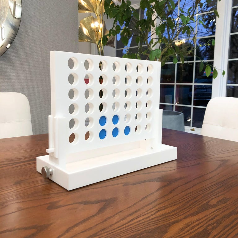 """The Classic game of Connect Four is reimagined. Crafted out of acrylic and lacquered white, the game features dark and light blue chips that are pleasing to the eye; allowing this piece to be kept out year round as decor.   Measurements  13"""" H x"""