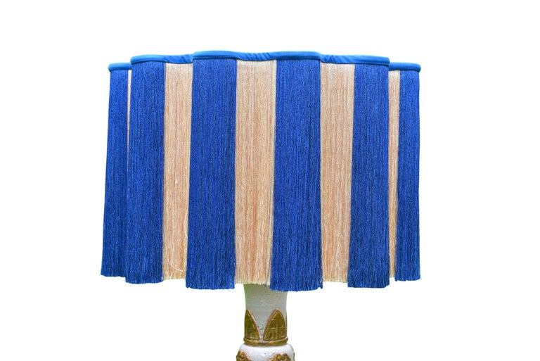 Stunning table lamp in white and gold chinoiserie inspired ceramic, made in France, circa 1960. With exquisite bespoke cream and blue fringe serpentine lamp shade.