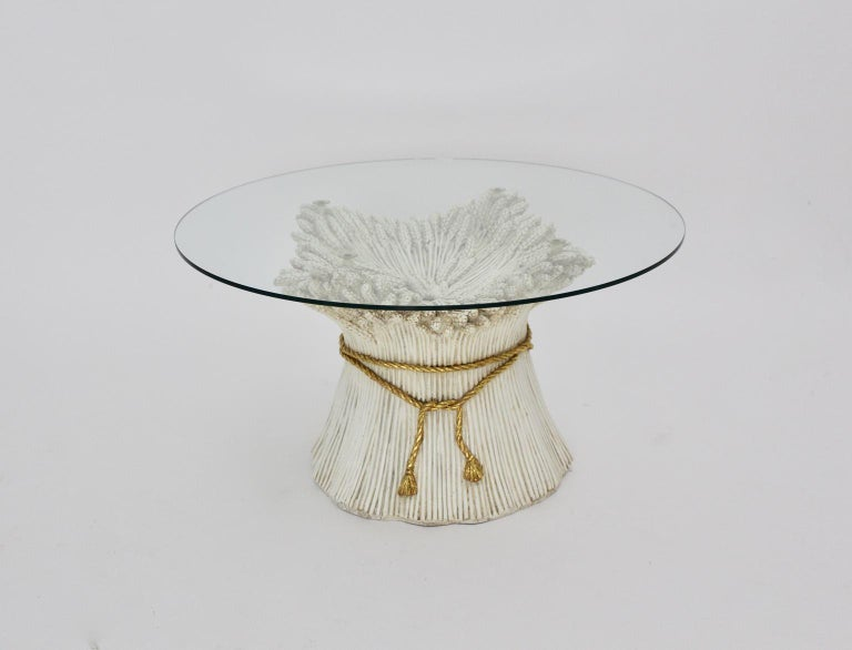 A white and gold Hollywood Regency Sheaf of Wheat coffee table, which was designed 1970s Italy. The white and gold colored coated ceramic coffee table shows a sheaf of wheat bundled with a golden rope. It features a clear glass top without