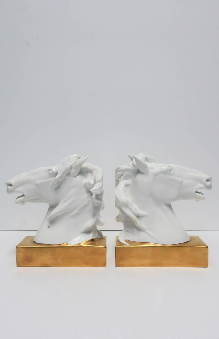 A pair of beautiful white and gold horse or equine porcelain bookends or decorative object sculptures. Pieces have beautiful detail in mane, snout, and ears. Marked on bottom