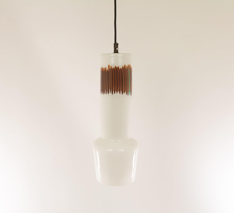 Hand blown white and red glass pendant no. 011.11 designed by Massimo Vignelli at the start of his impressive career in design and executed by Murano glass specialist Venini. One of the most characteristic lamps that Vignelli designed for