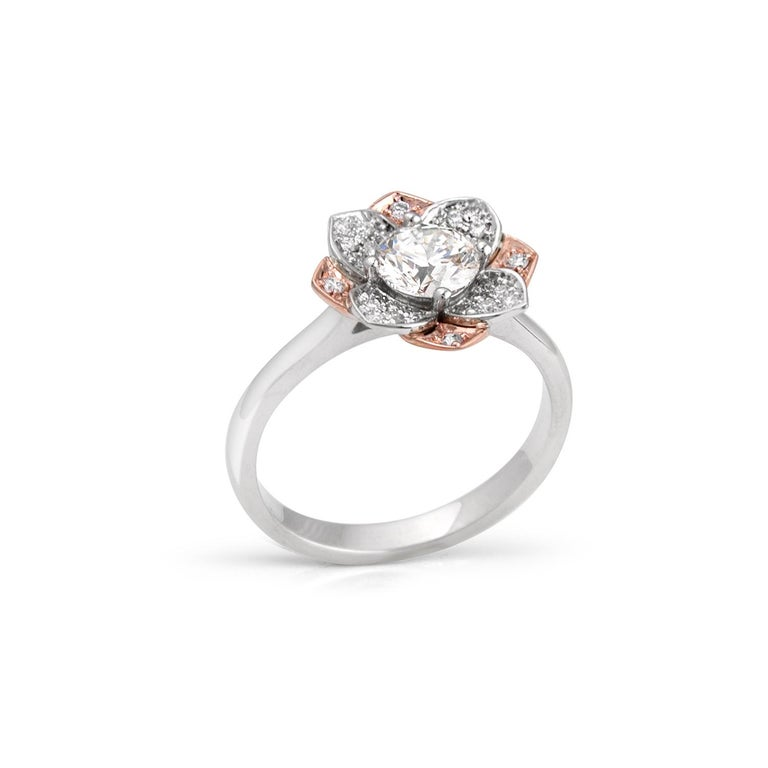 Flower ring in 14kt rose and white gold featuring a 0.70ct K VS1 round brilliant center diamond and pave' set petals with 28 diamonds equal to 0.19ct total. Ring size 6 1/2. Sizing up or down 2 sizes included in price. GIA number 2177065899.