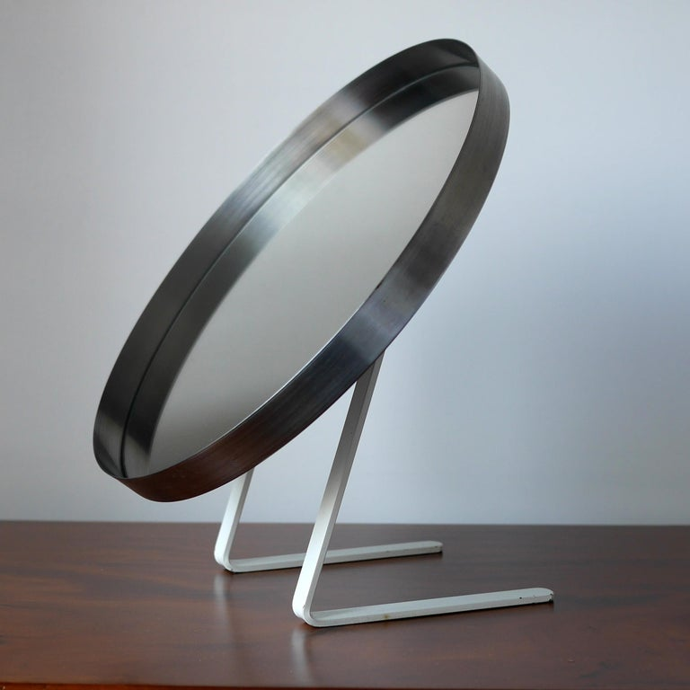 A rare vanity mirror by Owen F. Thomas for Durlston design Ltd circa 1968 in lovely original condition. Crafted from stainless steel with a lovely combination of steel mirror frame and original white enamel finish to the frame. The circular framed