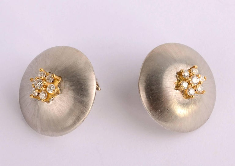 Delicate domed earrings in a slightly brushed white gold with 7 diamonds  set in yellow gold. They have much of the look of Buccellati without the corresponding price. The front is 18 karat gold with 14 karat clips. The clips can be converted to