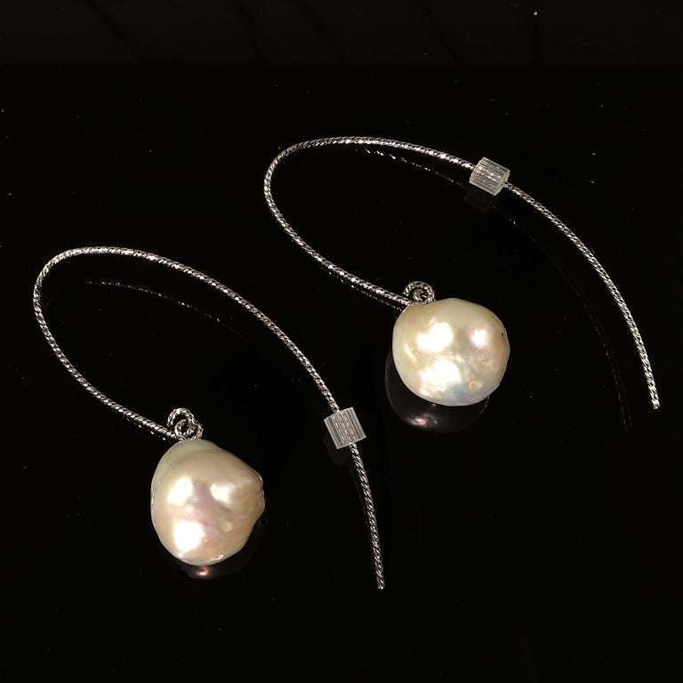 Custom made earrings of Iridescent White Baroque Pearls Dangling from twisted Sterling Silver Hooks.  The twisted wire sparkles and enhances the pearls. The Pearls are off Round and flash lovely shades of pink and yellow.  The Sterling Silver wires