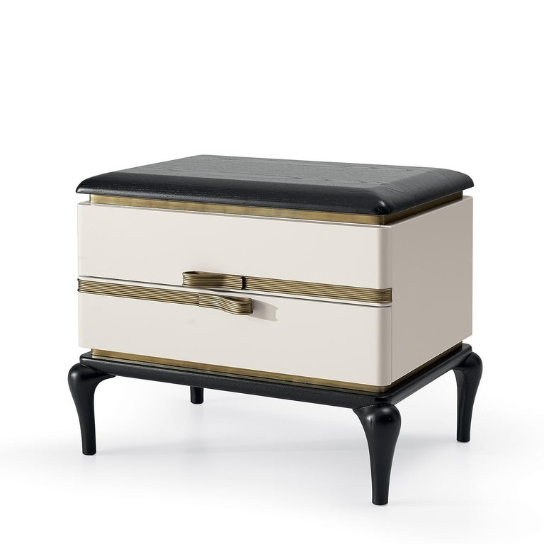 An elegant and sturdy piece of functional decor, this bedside table exudes a modern allure in its combination of black and white and burnished brass. A small piece with two drawers, it is composed of white-lacquered plywood and ash-veneered MDF