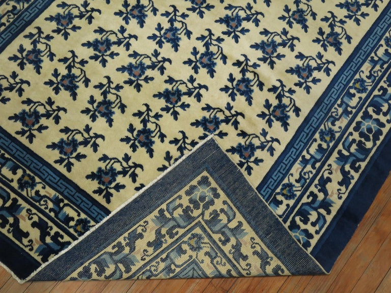 Floral vintage Chinese rug in shades of creamy white and blue.