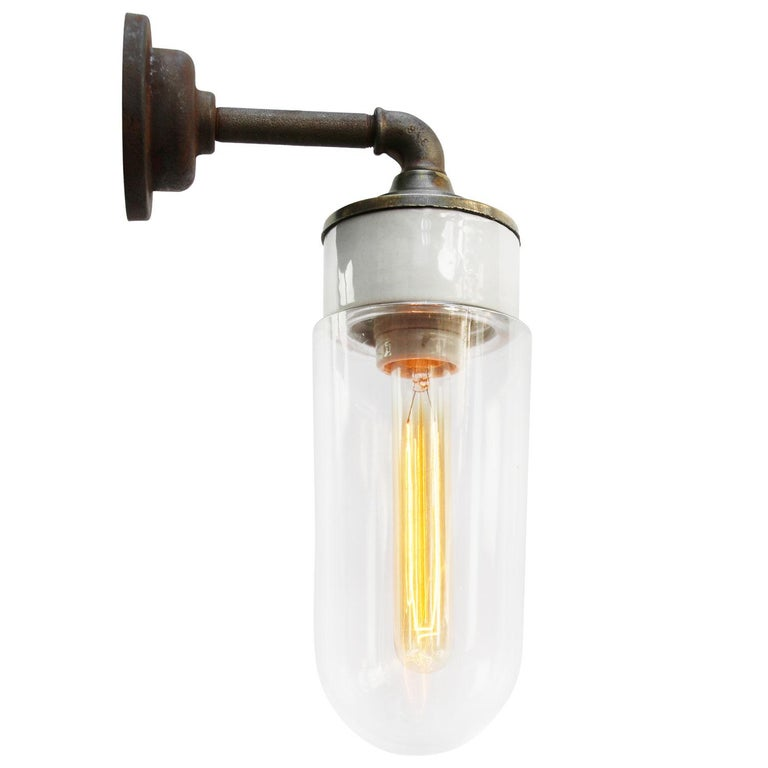 Porcelain Industrial wall lamp. White porcelain, brass and cast iron Clear glass. 2 conductors, no ground.  Diameter cast iron wall piece 10 cm. 2 holes to secure.  Weight: 2.10 kg / 4.6 lb  Priced per individual item. All lamps have been