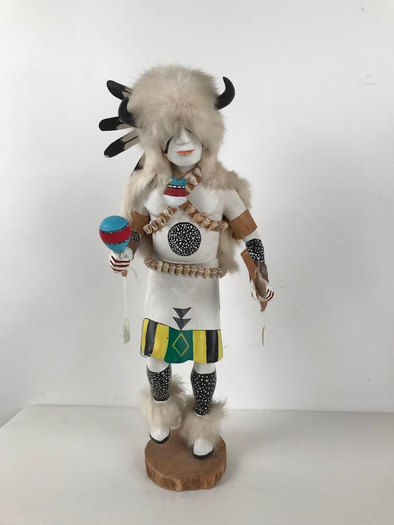 A stunning kachina katsina doll depicting White Buffalo in amazing detail, decorated with fur, feathers and sea shells, this is both a scared object but a fully realize work of art. The dancer is shown with a rattle in one hand and a bow in the