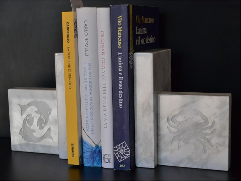 Bookends manufactured in White Carrara Italian marble with inlaid zodiac signs. You can choose the combination of the two signs, see on the diagram. weight: kilos 2.10 each one  For EU buyers this piece is subject to additional VAT tax, which