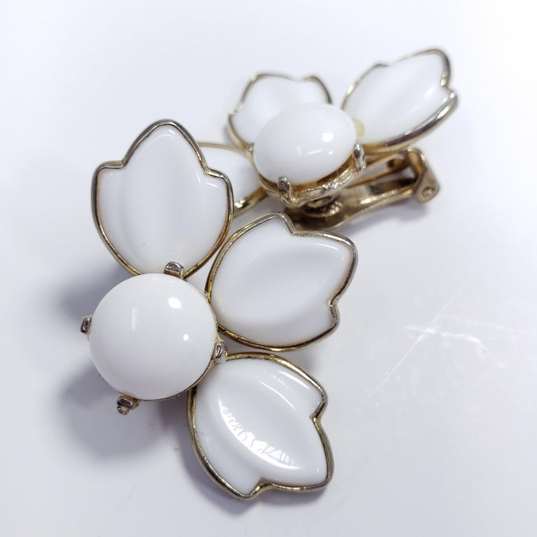 A pair of clip-on earrings featuring white glass petals, set in vintage goldtone metal. Sure to catch attention!