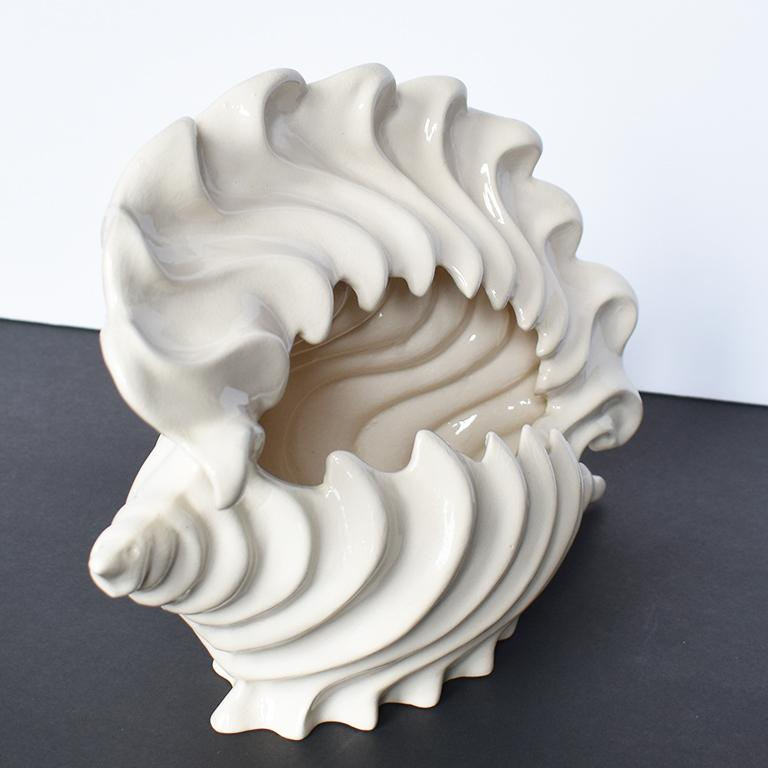 White ceramic seashell planter in the shape of a conch shell. A great way to add Hollywood Regency style to any patio or garden. 