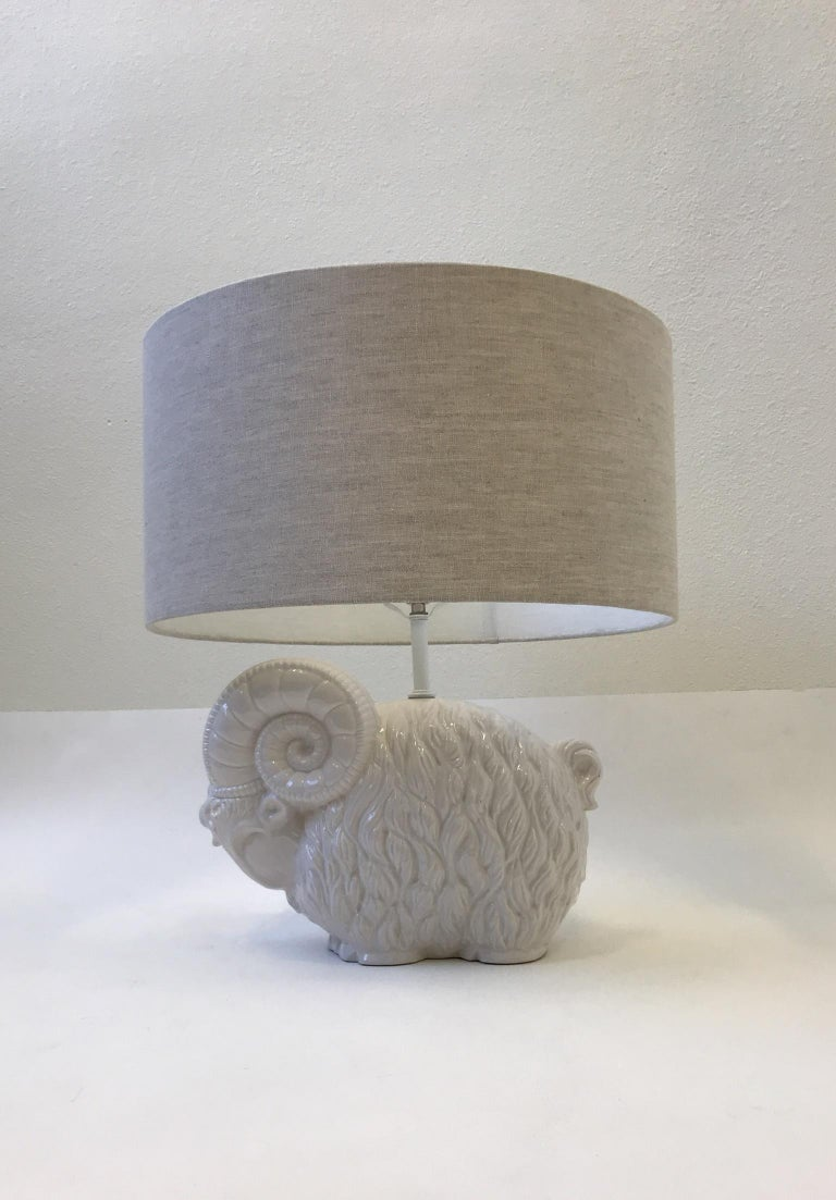 """A beautiful 1970's white ceramic table lamp designed by Hager. The lamp has been newly rewired with new polish nickel socket and new oatmeal linen shade.  Dim: Overall Dimensions- 22.5"""" high 20"""" diameter.   Just the Ram- 16"""" wide 11"""" high 7"""" deep."""