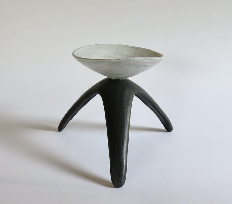 White cup chalice is a modern primitive ceramic piece, designed and hand built by the artist, Helena Starcevic. The cup has a dense white glaze over a dark clay body which adds depth to the glaze. The tripod legs have a matte black glaze with some