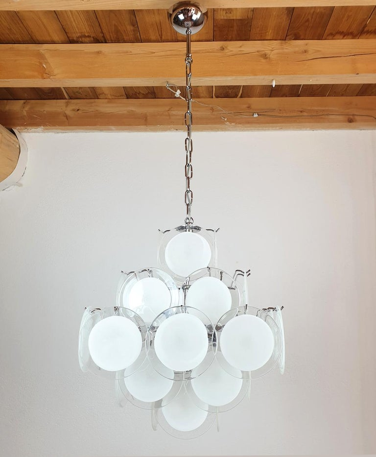 Vintage Modern hand blown murano glass chandelier, by Vistosi, Italy, circa 1980s. The Mid-Century Modern chandelier is made of white and clear Murano glass discs on a chrome frame. The shape is pyramidal, giving it a Mid Mod style. It has 6