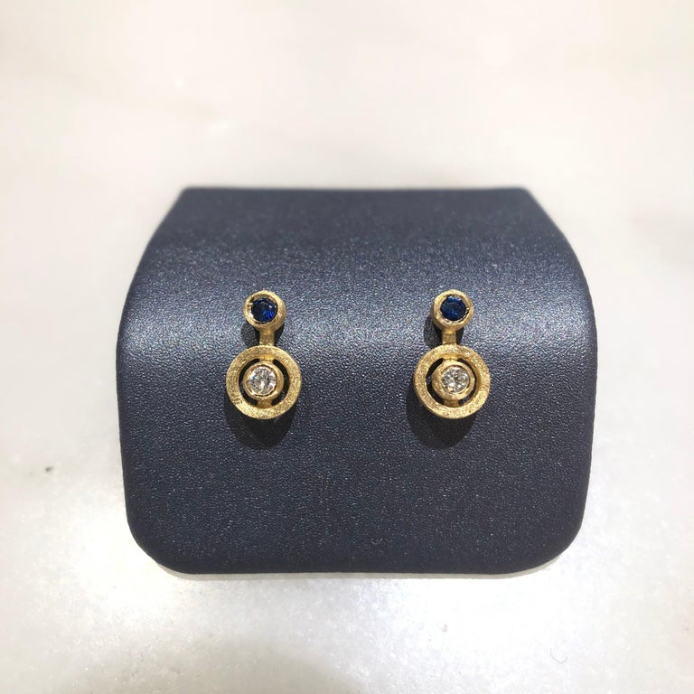 Nova Stud Earrings handcrafted in London by jewelry artist Shimell and Madden in satin-finished 18k yellow gold with 0.08 total carats of round brilliant-cut white diamonds and two vibrant blue sapphires, all bezel-set and attached to central 18k